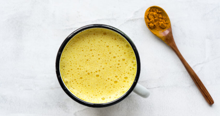 Turmeric latte, Golden milk. Hot healthy drink. Concrete background. Top view.