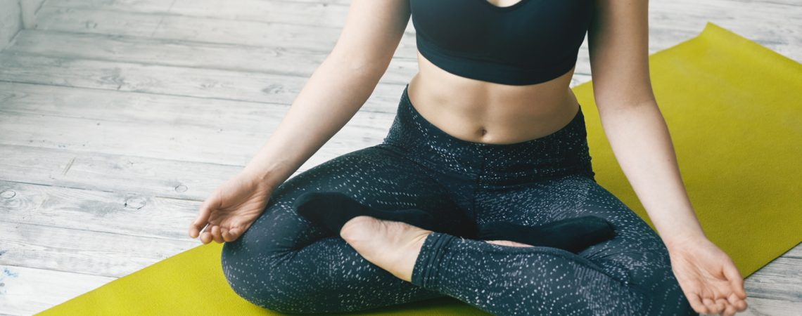 Cropped portrait of unrecognizable fit woman with athletic muscular body doing yoga meditation wearing stylish sports bra and leggings, sitting in lotus pose, keeping hands on top of her knees