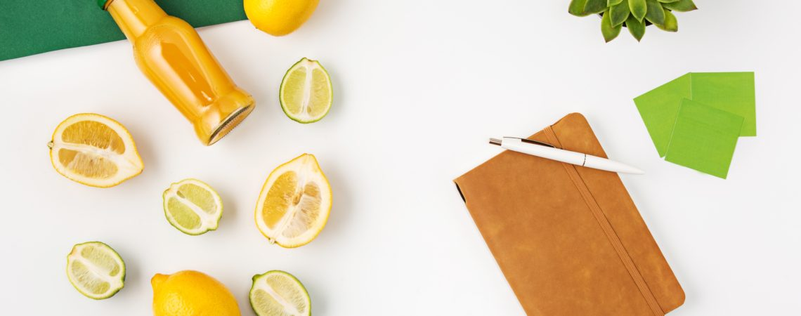 Top view of white female office table with diary notebook, fruits, pen on white